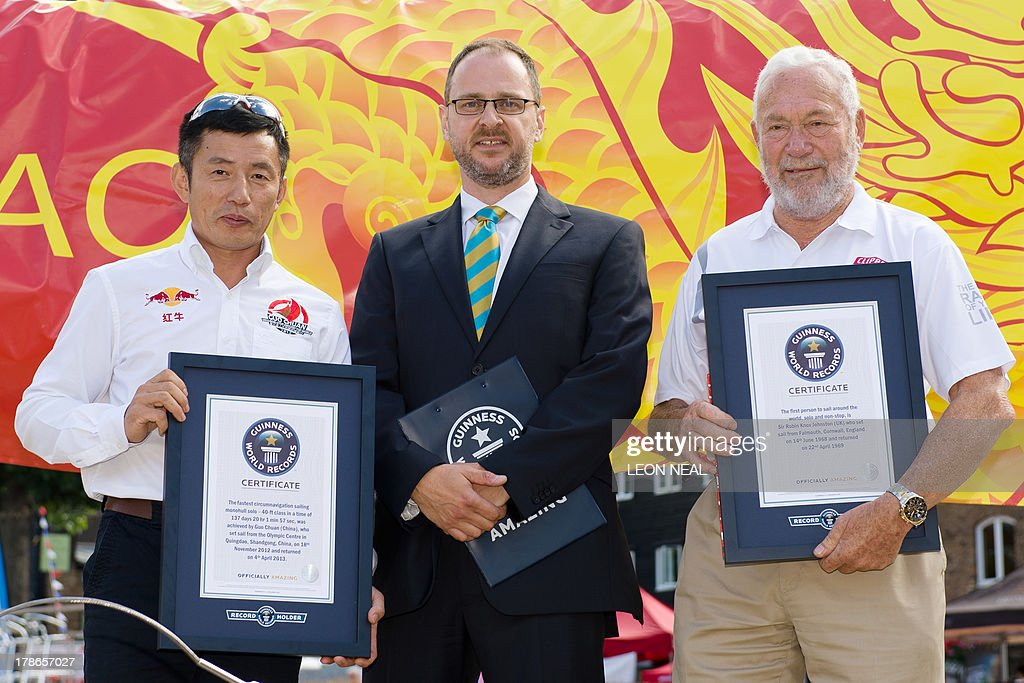 Guo Chuan (L), the first Chinese sailor to complete a solo circumnavigation of the world in 2013, and British sailor Robin Knox-Johnston (R), the first man to sail solo non-stop around the world in 1968-69, stand with their certificates in Saint Katherine's Dock in London on August 30, 2013, after being presented with Guinness World Record honours for their achievements. The Clipper 2013-14 Round the World Yacht Race starts September 1 from London and will return almost a year later after completing the 40,000-mile route.