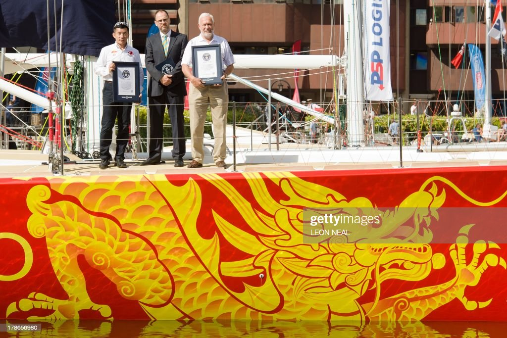 Guo Chuan, the first Chinese sailor to ever compete in the Clipper Round the World Yacht Race, (L) and Robin Knox-Johnston, the first man to sail solo non-stop around the world in 1968-69, (R) stand with their certificates in Saint Katherine's Dock in London on August 30, 2013, after being presented with Guinness World Record honours for their achievements. The Clipper 2013-14 Round the World Yacht Race starts September 1 from London and will return almost a year later after completing the 40,000-mile route. AFP PHOTO / LEON NEAL