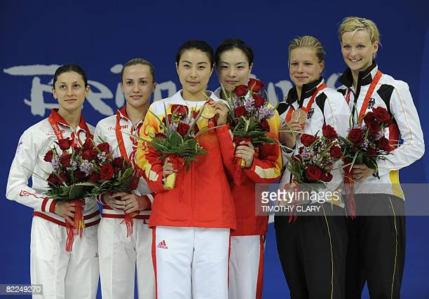 Guo Jingjing and Wu Minxia hold their gold medals with Silver medalists from Russia Julia Pakhalina and Anastasia Pozdnyakova along with Germany's...