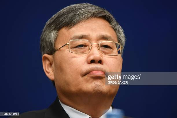 Guo Shuqing Chairman of the China Banking Regulatory Commission listens to a question at a press conference in Beijing on March 2 2017 / AFP PHOTO /...