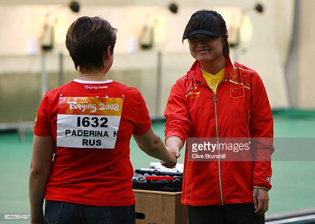 Guo Wenjun of China is congradulated for winning the gold medal by silver medalist Natalia Paderina of Russia after competing in the women's 10m air...