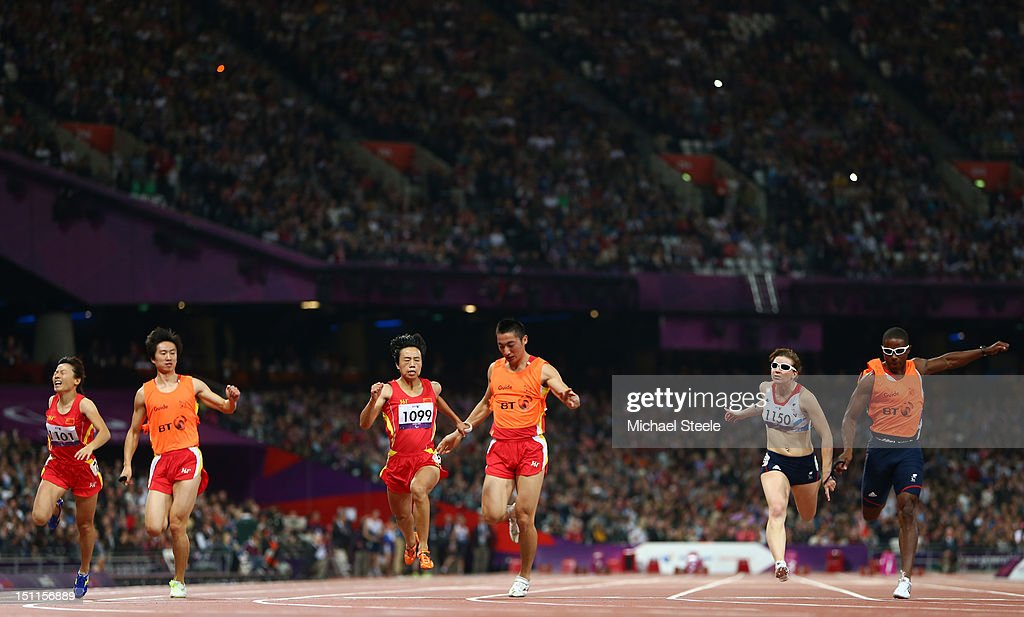 Guohua Zhou of China and her guide Jie Lie (C) cross the line first to win gold ahead of silver medalists <a gi-track='captionPersonalityLinkClicked' href=/galleries/search?phrase=Libby+Clegg&family=editorial&specificpeople=4307599 ng-click='$event.stopPropagation()'>Libby Clegg</a> of Great Britain and her guide Mikail Huggins and bronze medalists Daqing Zhou of China and her guide Hui Zhang in the Women's 100m - T12 Final on day 4 of the London 2012 Paralympic Games at Olympic Stadium on September 2, 2012 in London, England.