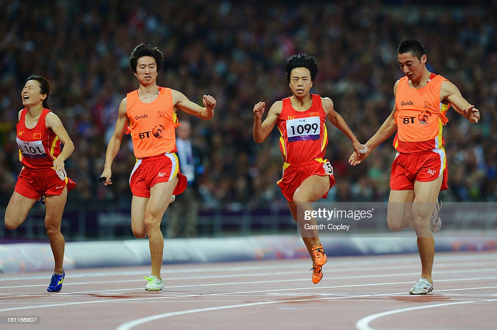 Guohua Zhou of China and her guide Jie Lie cross the line first to win gold ahead of bronze medalists Daqing Zhou of China and her guide Hui Zhang in the Women's 100m - T12 Final on day 4 of the London 2012 Paralympic Games at Olympic Stadium on September 2, 2012 in London, England.