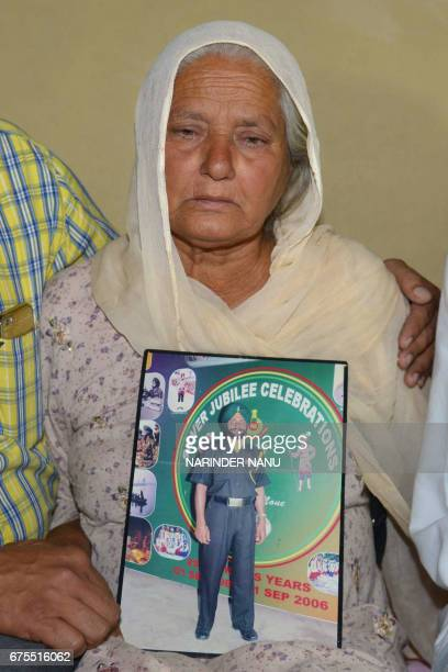 Gurinder Kaur mother of Indian army soldier Paramjeet Singh cries as she holds a picture of her son at her residence in Vein Pein village some 45 km...