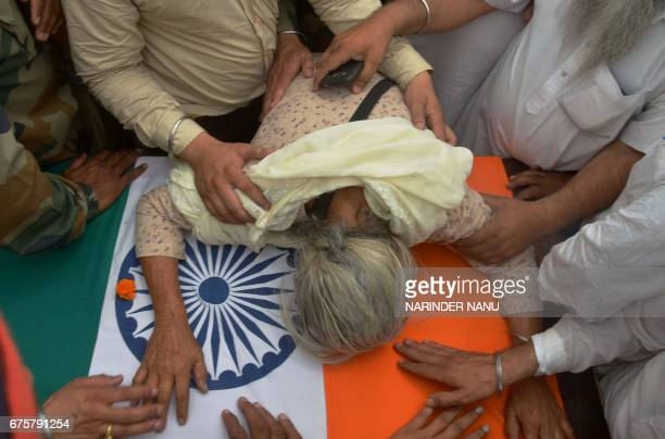 Gurinder Kaur the mother of Indian Army soldier Paramjeet Singh cries over his coffin during his funeral at Vein Pein village some 45kms from...