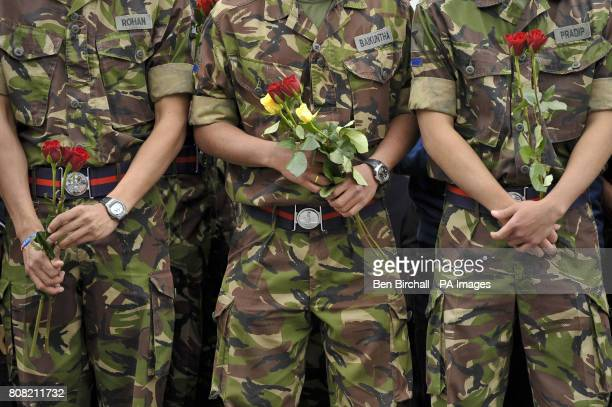 Gurkha soldiers hold red and yellow roses as they wait for the Union Flag draped coffins containing the bodies of Sapper Darren Foster of 21 Engineer...