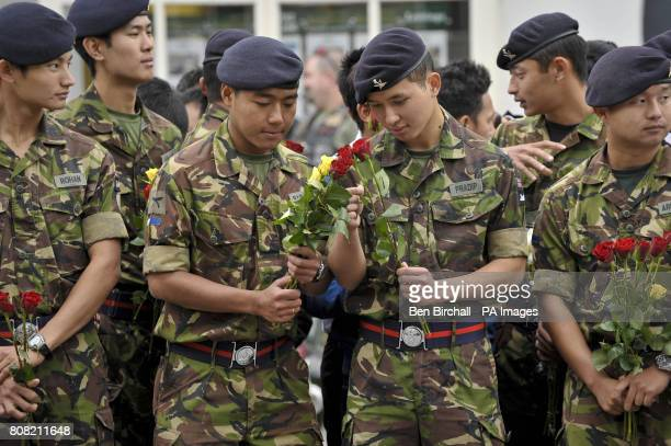 Gurkha soldiers inspect red and yellow roses as they wait for the Union Flag draped coffins containing the bodies of Sapper Darren Foster of 21...