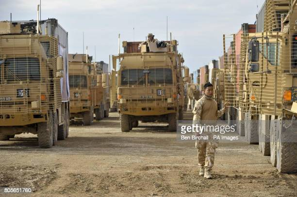 A Gurkha walks in between three lines of armoured Enhanced Palletised Loading System Vehicle that are preparing to carry out a Combat Logistics...