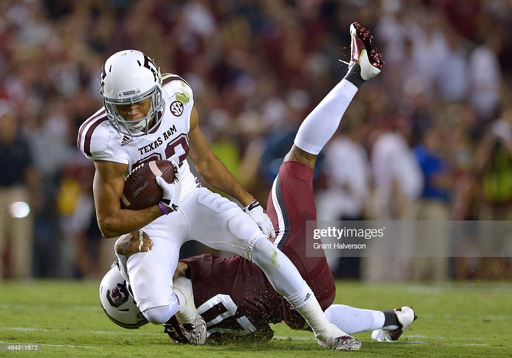 T.J. Gurley #20 of the South Carolina Gamecocks tackles Sabian Holmes #23 of the Texas A&M Aggies during their game at Williams-Brice Stadium on August 28, 2014 in Columbia, South Carolina. Texas A&M won 52-28.