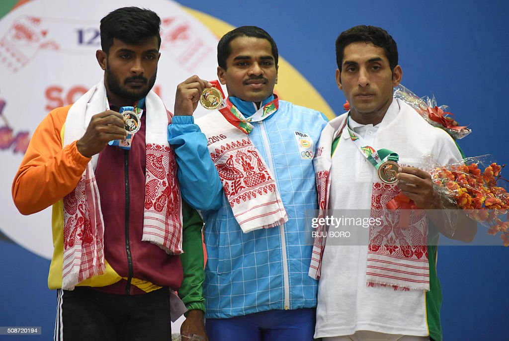 Guru Raja of India holds his gold medal next to silver medalist Chathuranga Lakmal Jayasooriya Archchilage (L) of Sri Lanka and bronze medalist Abdullah Ghafoor (R) of Pakistan at the 12th South Asian Games 2016 after the weightlifting 56 kg category at the Bhogeswari Phukanani Indoor Stadium in Dispur in Guwahati on February 6, 2016. AFP PHOTO/ Biju BORO / AFP / BIJU BORO