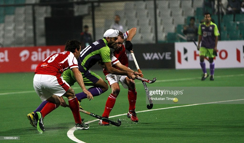 Gurvinder Chandi of Delhi Waveriders negotiates with the players of Mumbai Magician during Hockey India League match at Major Dhyan Chand National Stadium on January 16, 2013 in New Delhi, India.