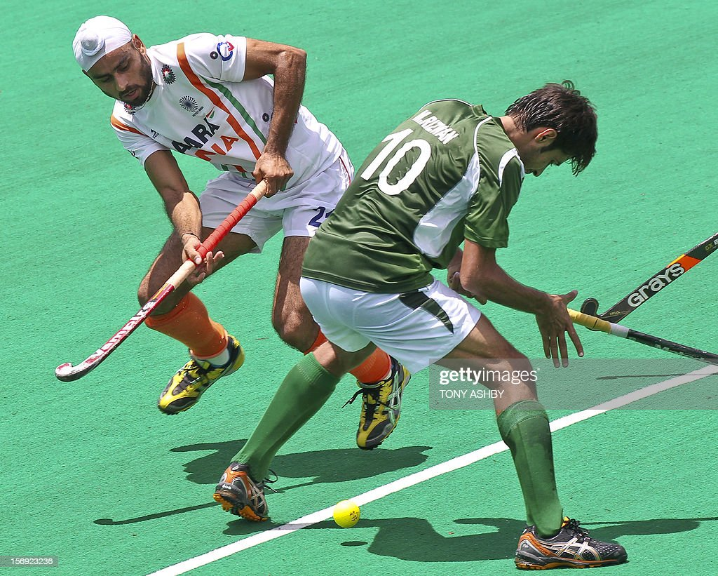 Gurvinder Singh Chandi of India (rear) passes the ball between the legs of Muhammad Rizwan of Pakistan (front) during their match on the final day of the International Super Series hockey tournament in Perth on November 25, 2012. AFP PHOTO / Tony ASHBY IMAGE