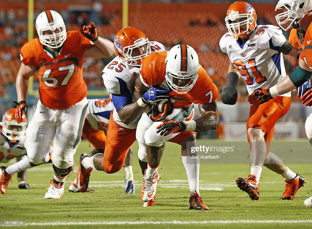 Gus Edwards #7 of the Miami Hurricanes carries Marquis Smith #25 of the Savannah State Tigers into the end zone as he scores a touchdown on September 21, 2013 at Sun Life Stadium in Miami Gardens, Florida. Miami defeated Savannah State 77-7.