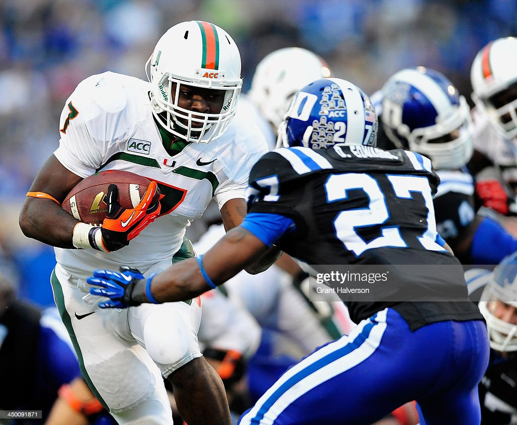 Gus Edwards #7 of the Miami Hurricanes runs against DeVon Edwards #27 of the Duke Blue Devils during play at Wallace Wade Stadium on November 16, 2013 in Durham, North Carolina.