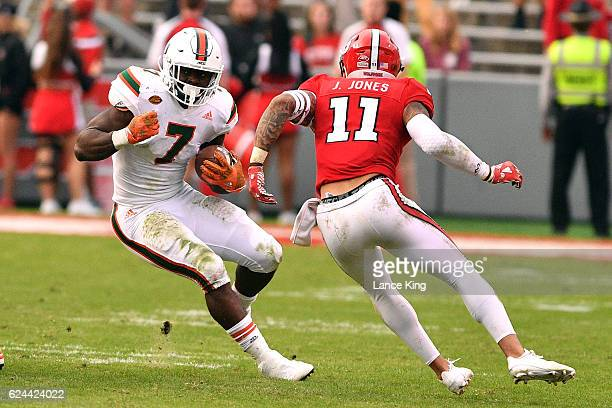 Gus Edwards of the Miami Hurricanes runs with the ball against Josh Jones of the North Carolina State Wolfpack at CarterFinley Stadium on November 19...