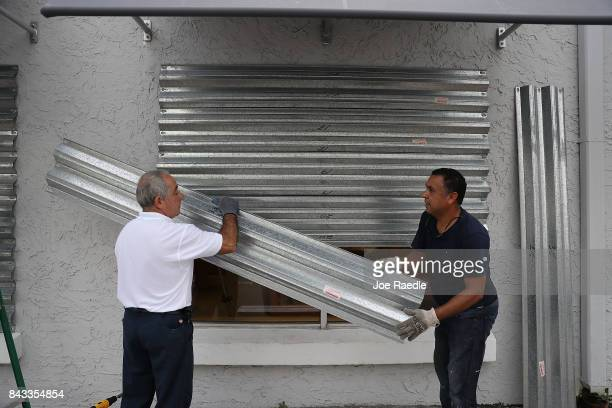 Gus Sousa and Winston Mora put hurricane shutters on a business as they prepare for Hurricane Irma on September 6 2017 in Miami Florida It's still...