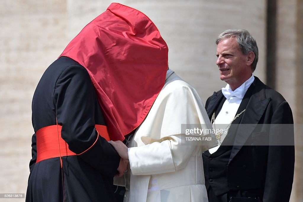 A gust of wind lifts the mantilla of an unidentified cardinal as he shakes hands with Pope Francis at the end of an audience as part of the Jubilee Year of Mercy on April 30, 2016 at St Peter's square in Vatican.
