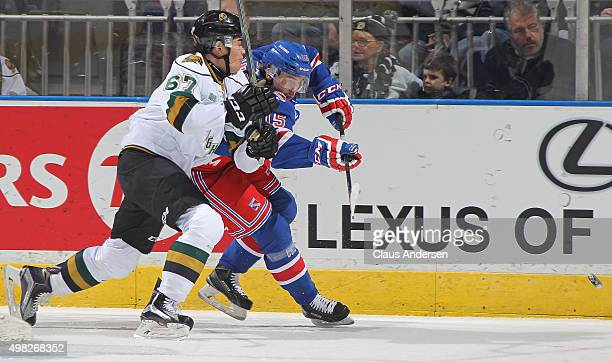 Gustaf Franzen of the Kitchener Rangers gets rid of the puck just before being hit by Kole Sherwood of the London Knights during an OHL game at...