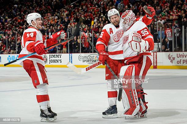 Gustav Nyquist and Niklas Kronwall celebrate with goalie Jimmy Howard of the Detroit Red Wings after defeating the Chicago Blackhawks 32 during the...
