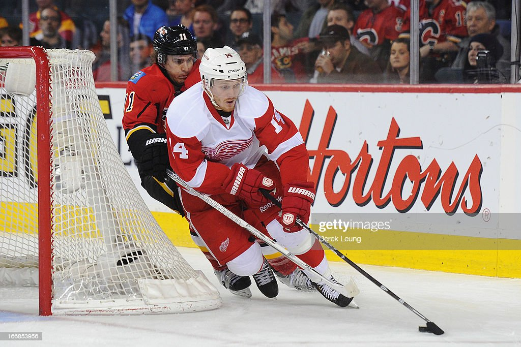 Gustav Nyquist #14 of the Detroit Red Wings carries the puck against <a gi-track='captionPersonalityLinkClicked' href=/galleries/search?phrase=Mikael+Backlund&family=editorial&specificpeople=4324942 ng-click='$event.stopPropagation()'>Mikael Backlund</a> #11 of the Calgary Flames during an NHL game at Scotiabank Saddledome on April 17, 2013 in Calgary, Alberta, Canada.