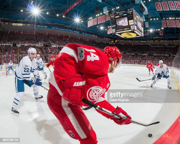 Gustav Nyquist of the Detroit Red Wings controls the puck in front of Nikita Zaitsev and Kasperi Kapanen of the Toronto Maple Leafs during an NHL...