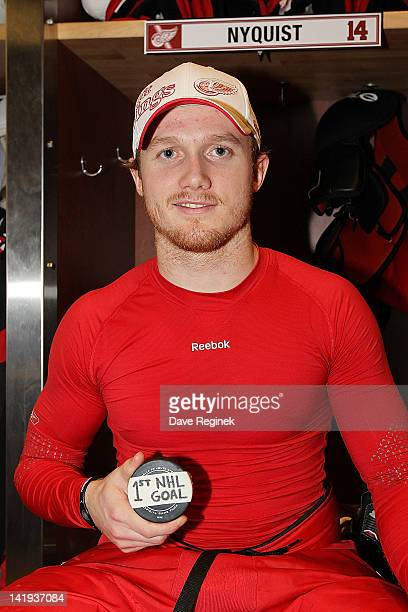 Gustav Nyquist of the Detroit Red Wings holds his first ever NHL goal puck in front of his locker after an NHL game against Columbus Blue Jackets at...