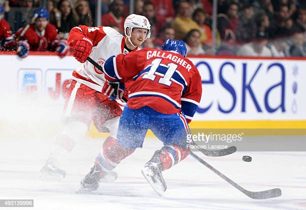 Gustav Nyquist of the Detroit Red Wings passes the puck against Brendan Gallagher of the Montreal Canadiens in the NHL game at the Bell Centre on...