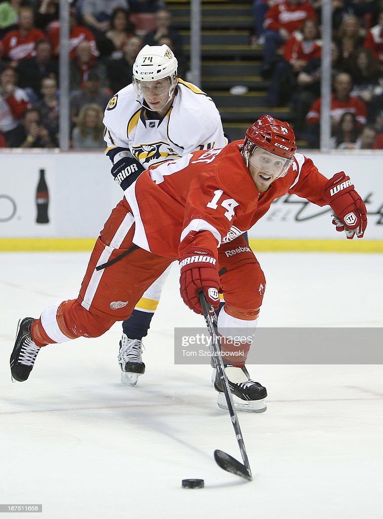 <a gi-track='captionPersonalityLinkClicked' href=/galleries/search?phrase=Gustav+Nyquist&family=editorial&specificpeople=5491209 ng-click='$event.stopPropagation()'>Gustav Nyquist</a> #14 of the Detroit Red Wings reaches for a loose puck during an NHL game as <a gi-track='captionPersonalityLinkClicked' href=/galleries/search?phrase=Sergei+Kostitsyn&family=editorial&specificpeople=599906 ng-click='$event.stopPropagation()'>Sergei Kostitsyn</a> #74 of the Nashville Predators checks him at Joe Louis Arena on April 25, 2013 in Detroit, Michigan.