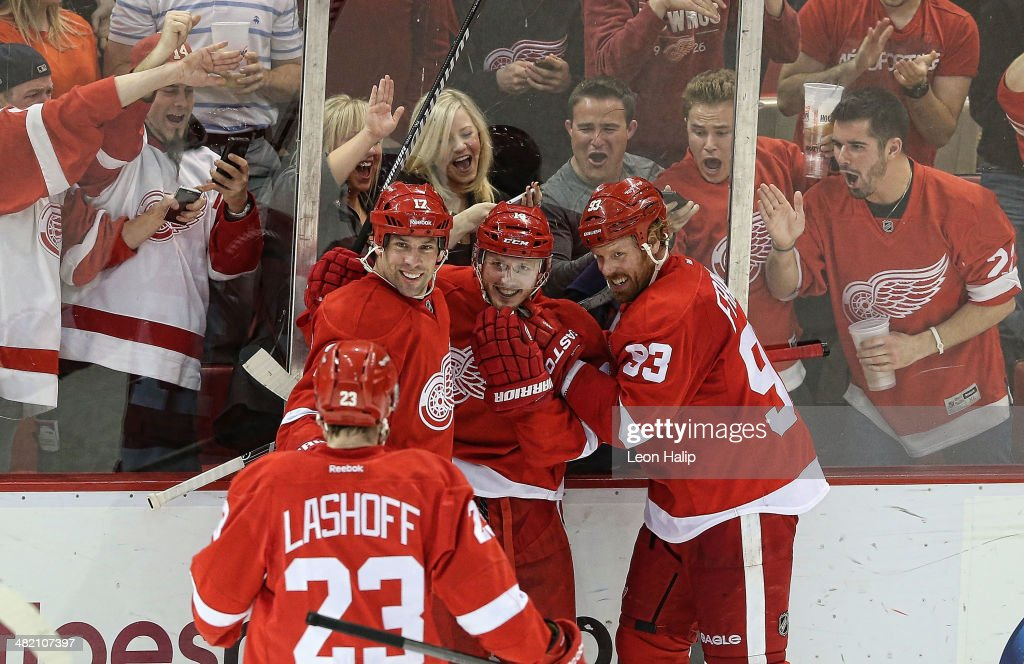Gustav Nyquist #14 of the Detroit Red Wings scores a third period game winning goal and is congratulated by his teammates during the game against the Boston Bruins at Joe Louis Arena on April 2, 2014 in Detroit, Michigan. The Red Wings defeated the Bruins 3-2