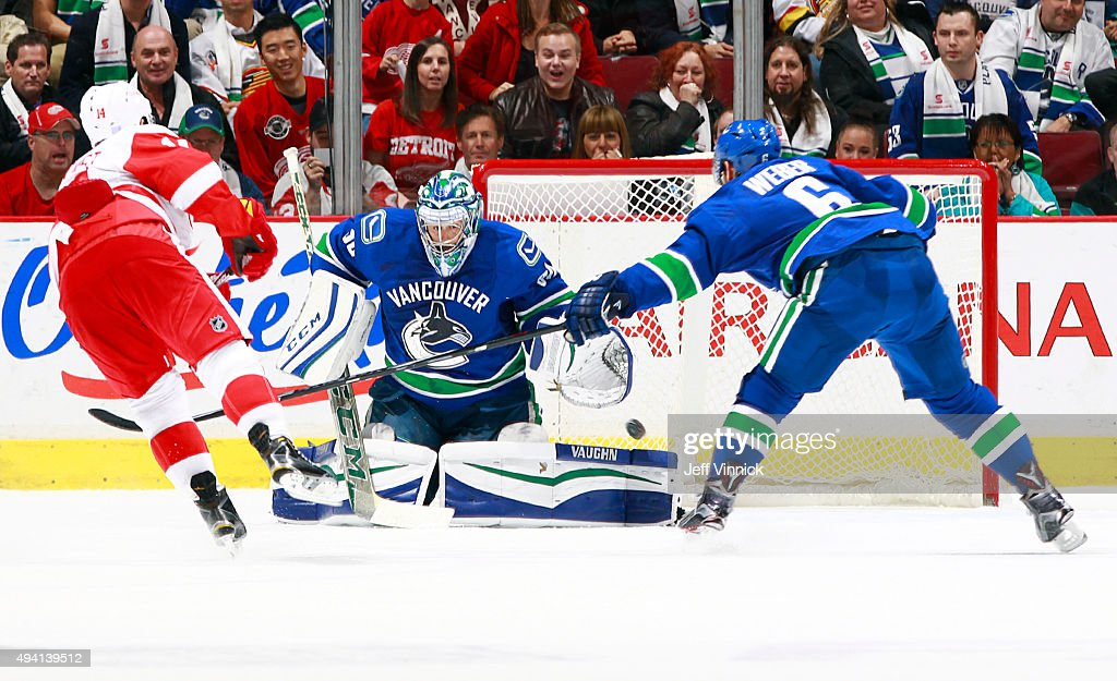 Gustav Nyquist #14 of the Detroit Red Wings scores in overtime on Ryan Miller #30 of the Vancouver Canucks as Yannick Weber #6 of the Canucks reaches to stop him during their NHL game at Rogers Arena October 24, 2015 in Vancouver, British Columbia, Canada. Detroit won 3-2.