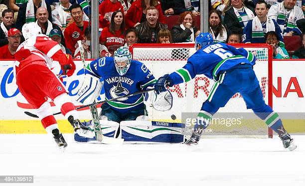 Gustav Nyquist of the Detroit Red Wings scores in overtime on Ryan Miller of the Vancouver Canucks as Yannick Weber of the Canucks reaches to stop...