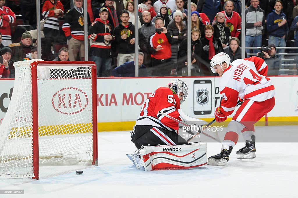 Gustav Nyquist of the Detroit Red Wings scores in the shootout on goalie Corey Crawford of the Chicago Blackhawks during the NHL game at the United...