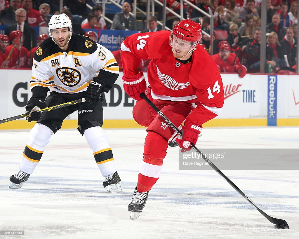 Gustav Nyquist of the Detroit Red Wings shoots the puck as Patrice Bergeron of the Boston Bruins skates behind during Game Three of the First Round...
