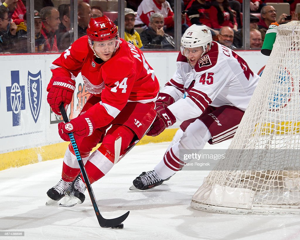 Gustav Nyquist of the Detroit Red Wings skates around the net with the puck as Andrew Campbell of the Arizona Coyotes gives chase during a NHL game...