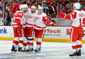 Gustav Nyquist of the Detroit Red Wings skates in to celebrate with teammates Joakim Andersson Jakub Kindl Carlo Colaiacovo and Damien Brunner after...
