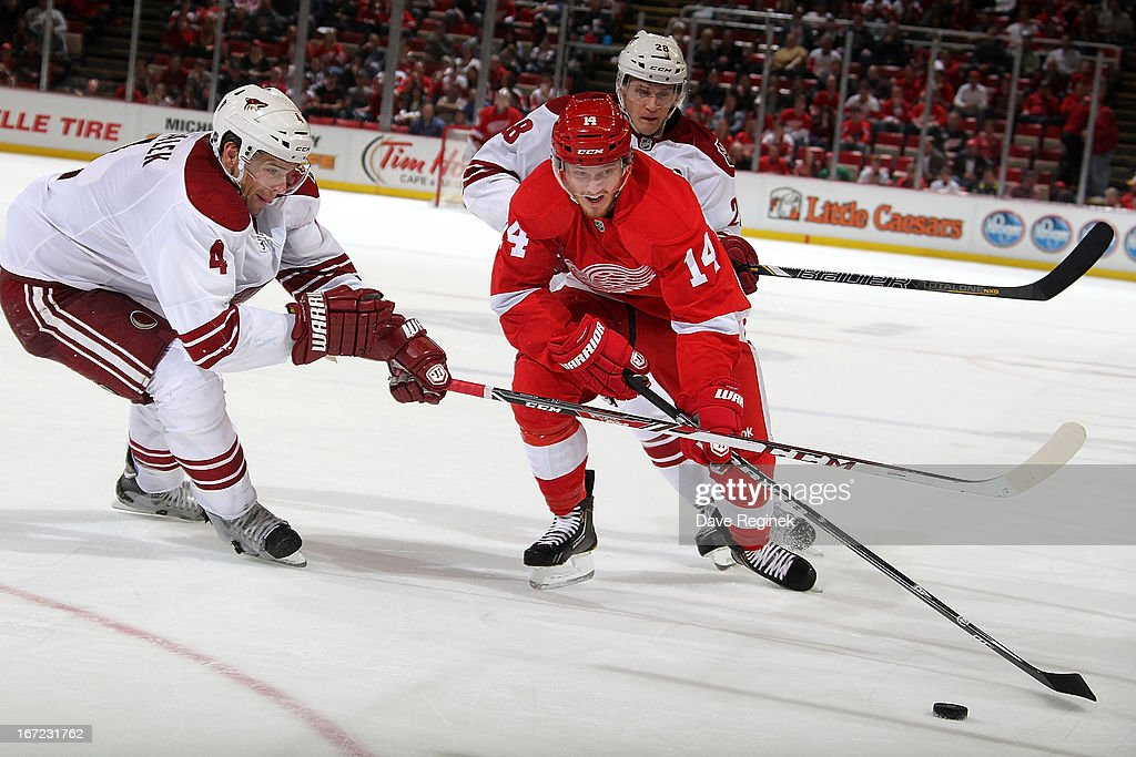 <a gi-track='captionPersonalityLinkClicked' href=/galleries/search?phrase=Gustav+Nyquist&family=editorial&specificpeople=5491209 ng-click='$event.stopPropagation()'>Gustav Nyquist</a> #14 of the Detroit Red Wings skates with the puck between <a gi-track='captionPersonalityLinkClicked' href=/galleries/search?phrase=Zbynek+Michalek&family=editorial&specificpeople=243230 ng-click='$event.stopPropagation()'>Zbynek Michalek</a> #4 and <a gi-track='captionPersonalityLinkClicked' href=/galleries/search?phrase=Lauri+Korpikoski&family=editorial&specificpeople=2108074 ng-click='$event.stopPropagation()'>Lauri Korpikoski</a> #28 of the Phoenix Coyotes during a NHL game at Joe Louis Arena on April 22, 2013 in Detroit, Michigan. Detroit defeated Phoenix 4-0