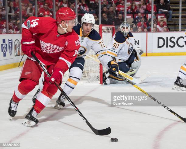 Gustav Nyquist of the Detroit Red Wings skates with the puck followed by Evan Rodrigues of the Buffalo Sabres as goaltender Robin Lehner of the...