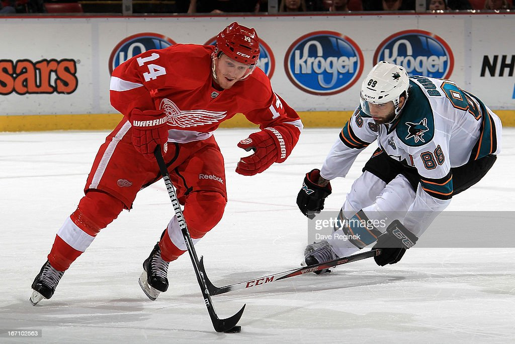 Gustav Nyquist #14 of the Detroit Red Wings skates with the puck in front of <a gi-track='captionPersonalityLinkClicked' href=/galleries/search?phrase=Brent+Burns&family=editorial&specificpeople=212883 ng-click='$event.stopPropagation()'>Brent Burns</a> #88 of the San Jose Sharks during an NHL game at Joe Louis Arena on April 11, 2013 in Detroit, Michigan. San Jose defeated Detroit 3-2 in a shoot-out