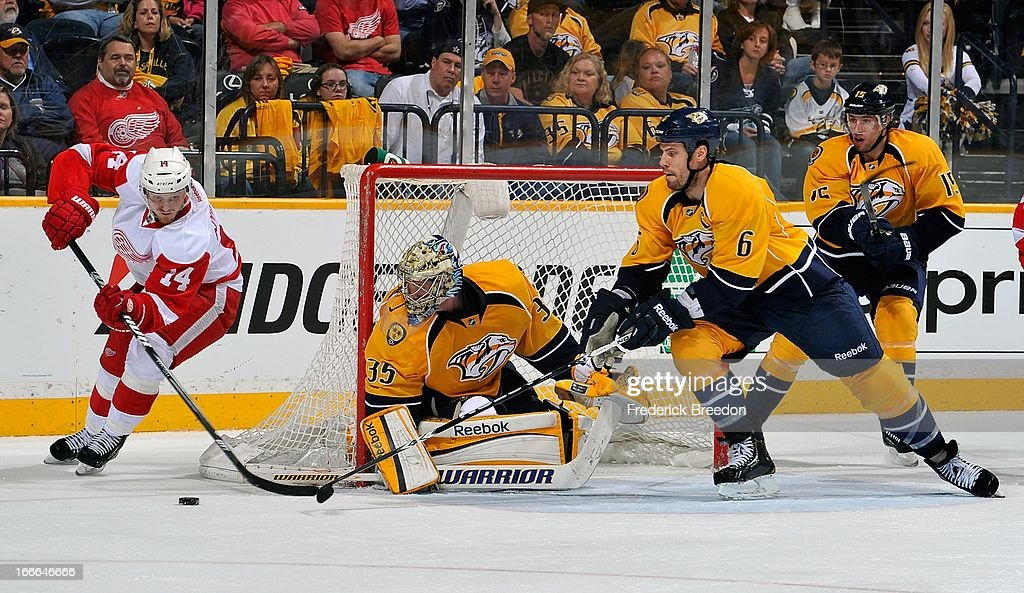 Gustav Nyquist #14 of the Detroit Red Wings tries a wrap around on goalie <a gi-track='captionPersonalityLinkClicked' href=/galleries/search?phrase=Pekka+Rinne&family=editorial&specificpeople=2118342 ng-click='$event.stopPropagation()'>Pekka Rinne</a> #35 of the Nashville Predators in front of Predators defenceman <a gi-track='captionPersonalityLinkClicked' href=/galleries/search?phrase=Shea+Weber&family=editorial&specificpeople=554412 ng-click='$event.stopPropagation()'>Shea Weber</a> #6 at the Bridgestone Arena on April 14, 2013 in Nashville, Tennessee.