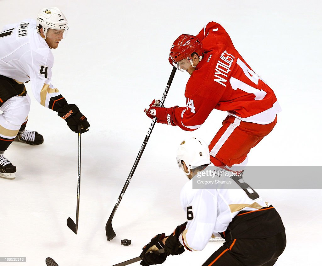 <a gi-track='captionPersonalityLinkClicked' href=/galleries/search?phrase=Gustav+Nyquist&family=editorial&specificpeople=5491209 ng-click='$event.stopPropagation()'>Gustav Nyquist</a> #14 of the Detroit Red Wings tries to split the defense of <a gi-track='captionPersonalityLinkClicked' href=/galleries/search?phrase=Cam+Fowler&family=editorial&specificpeople=5484080 ng-click='$event.stopPropagation()'>Cam Fowler</a> #4 and <a gi-track='captionPersonalityLinkClicked' href=/galleries/search?phrase=Ben+Lovejoy&family=editorial&specificpeople=4509565 ng-click='$event.stopPropagation()'>Ben Lovejoy</a> #6 of the Anaheim Ducks in Game Six of the Western Conference Quarterfinals during the 2013 NHL Stanley Cup Playoffs at Joe Louis Arena on May 10, 2013 in Detroit, Michigan. Detroit won the game in overtime 4-3 to tie the series 3-3.