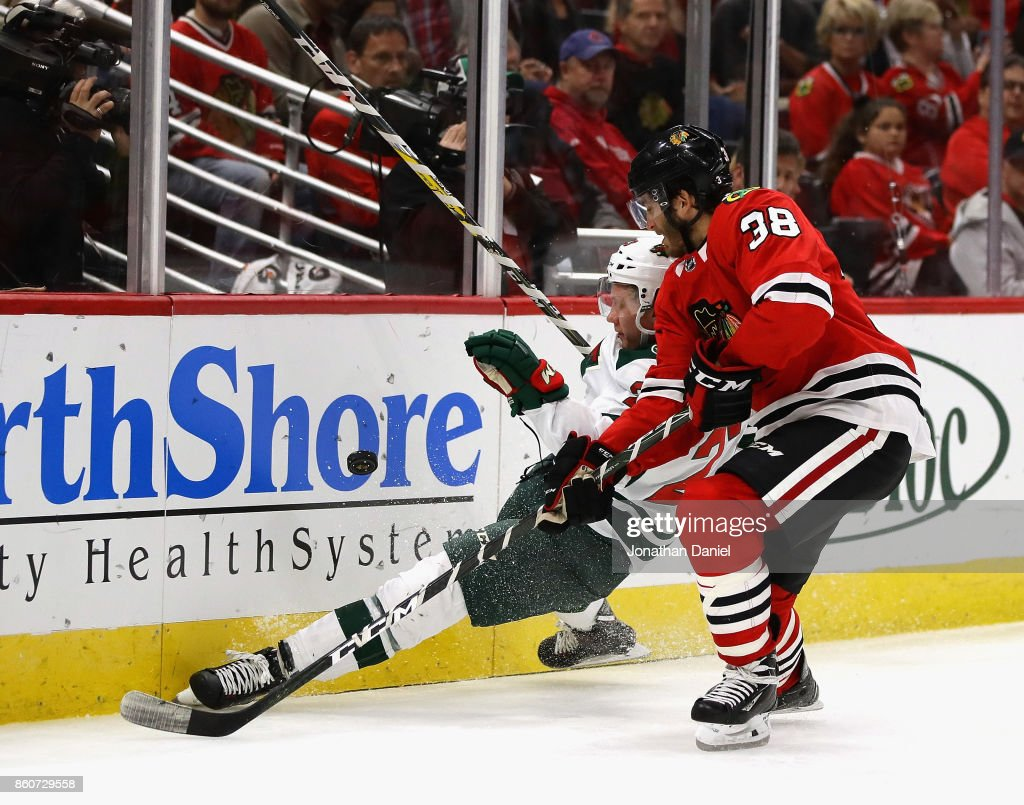 Gustav Olofsson #23 of the Minnesota Wild slips as he goes for the puck under pressue from Ryan Hartman #38 of the Chicago Blackhawks at the United Center on October 12, 2017 in Chicago, Illinois. The Wild defeated the Blackhawks 5-2.