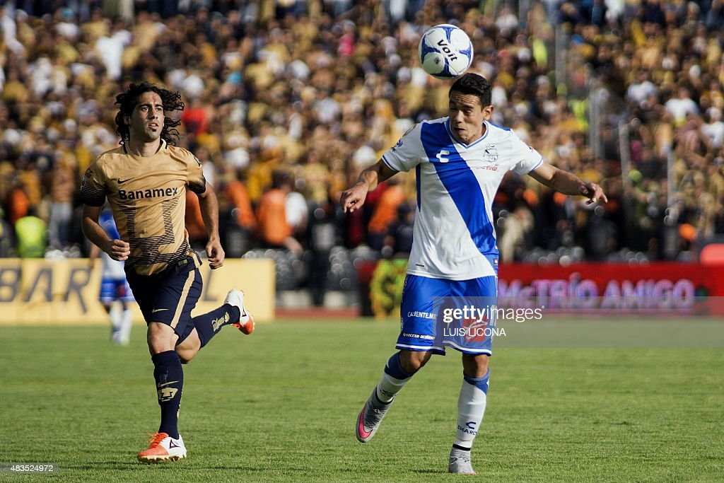 Gustavo Alustiza of Puebla vies for the ball with Matias Britos of Pumas during their Mexican Apertura football tournament in Puebla Puebla State...