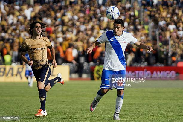 Gustavo Alustiza of Puebla vies for the ball with Matias Britos of Pumas during their Mexican Apertura football tournament in Puebla Puebla State...
