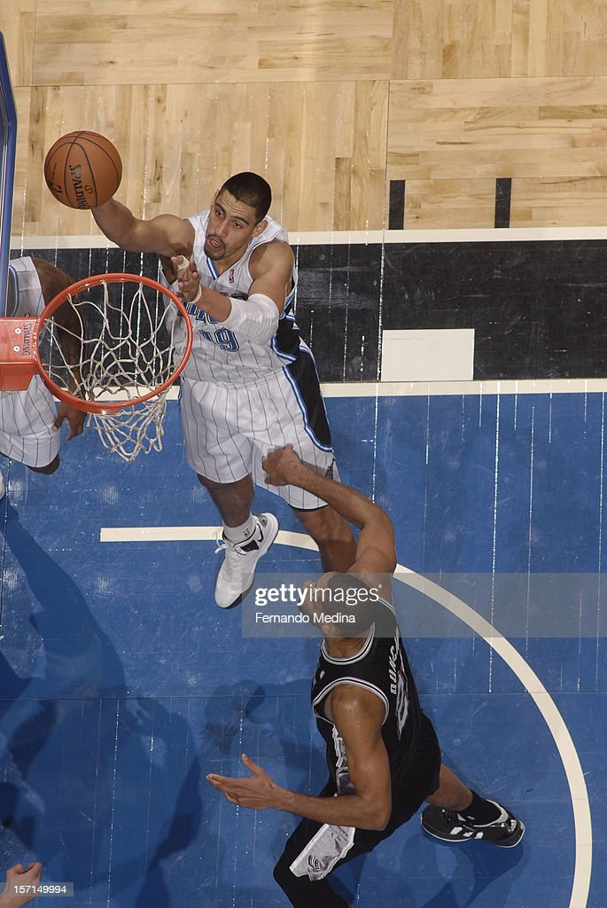 <a gi-track='captionPersonalityLinkClicked' href=/galleries/search?phrase=Gustavo+Ayon&family=editorial&specificpeople=4474343 ng-click='$event.stopPropagation()'>Gustavo Ayon</a> #19 of the Orlando Magic goes to the basket against <a gi-track='captionPersonalityLinkClicked' href=/galleries/search?phrase=Tim+Duncan&family=editorial&specificpeople=201467 ng-click='$event.stopPropagation()'>Tim Duncan</a> #21 of the San Antonio Spurs during the game between the San Antonio Spurs and the Orlando Magic on November 28, 2012 at Amway Center in Orlando, Florida.