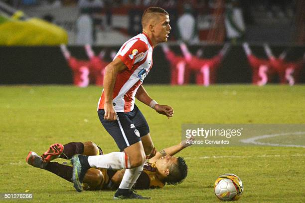 Gustavo Cuellar of Junior controls the ball as Robin Ramirez of Tolima falls during a first leg match between Deportes Tolima and Ateltico Junior as...