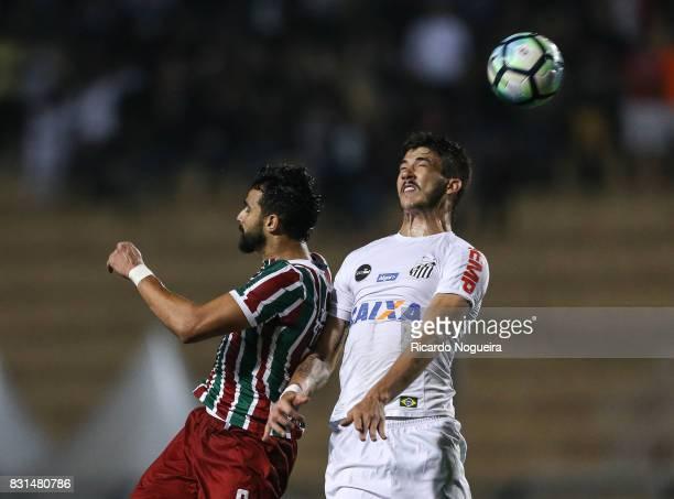 Gustavo Henrique of Santos battles for the ball with Henrique Dourado of Fluminense during the match between Santos and Fluminense as a part of...