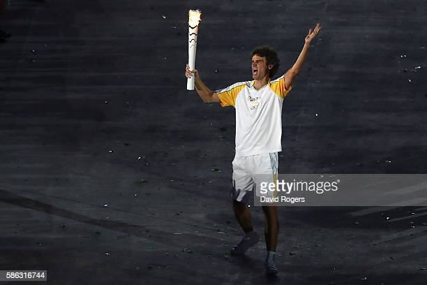 Gustavo Kuerten of Brazil carries the Olympic torch during the Opening Ceremony of the Rio 2016 Olympic Games at Maracana Stadium on August 5 2016 in...