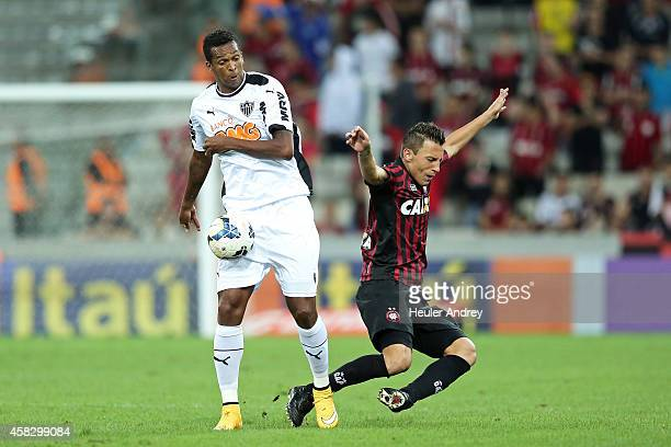 Gustavo of AtleticoPR competes for the ball with Jo of AtleticoMG during the match between AtleticoPR and AtleticoMG for the Brazilian Series A 2014...