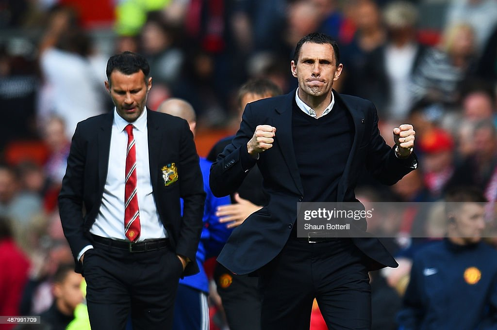 <a gi-track='captionPersonalityLinkClicked' href=/galleries/search?phrase=Gustavo+Poyet&family=editorial&specificpeople=227352 ng-click='$event.stopPropagation()'>Gustavo Poyet</a> the Sunderland manager celebrates his team's 1-0 victory as a dejected <a gi-track='captionPersonalityLinkClicked' href=/galleries/search?phrase=Ryan+Giggs&family=editorial&specificpeople=201666 ng-click='$event.stopPropagation()'>Ryan Giggs</a> the Manchester United interim manager walks behind during the Barclays Premier League match between Manchester United and Sunderland at Old Trafford on May 3, 2014 in Manchester, England.