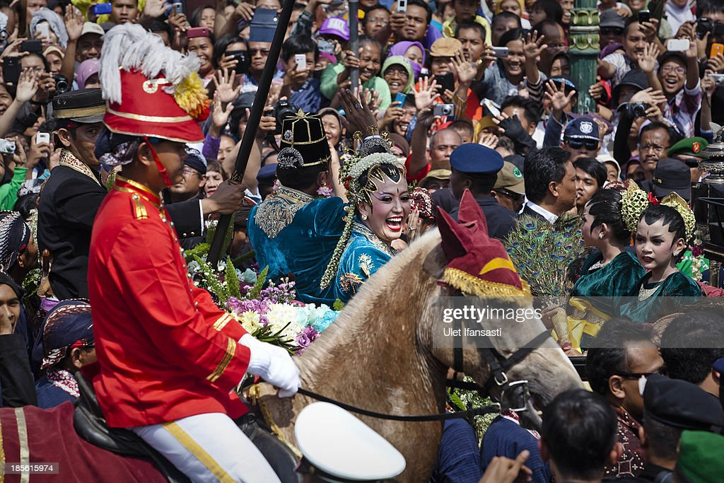 Gusti Kanjeng Ratu Hayu and KPH Notonegoro wave to crowds while on their journey by carriage during the wedding ceremony parade as part of the Royal Wedding Held For Sultan Hamengkubuwono X's Daughter Gusti Ratu Kanjeng Hayu And KPH Notonegoro on October 23, 2013 in Yogyakarta, Indonesia. Wedding celebrations will take place October 21-23 October. The wedding parade will include 12 royal horse drawn carriages and will be streamed live on the internet so that it can be watched by people all over the world.